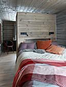Gemütliches Bett vor einer Holzwand als Raumteiler