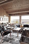 Chalet-Wohnzimmer mit grauen Accessoires und Holzverkleidung