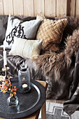 Fur blanket and cushions on sofa behind autumnal arrangement on coffee table