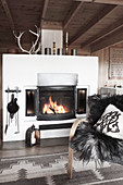 Fire in fireplace in open-plan living room with grey accessories