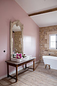 Sink with peonies in front of antique mirror on pink wall in bathroom