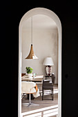 View through round arch on dining table, chair, bench and side table with table lamp