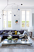 Vintage mobile over upholstered sofa with cushions and glass-topped coffee table in bright living room