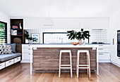 Open kitchen with kitchen island and bar stools, side bench with overlay and drawer