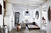 Walled-up fireplace, day bed, pallet, chest and stool in a rustic living room