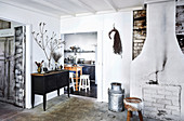 Brick wall, stool, milk can and sideboard in front of the passage
