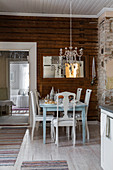 Set table and chairs below chandelier decorated with old silver cutlery
