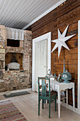 Console table below white star on wall in front of rustic brick fireplace