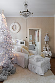 White Christmas tree and white loose-covered armchair with matching footstool