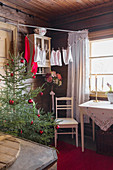 Christmas tree decorated with red baubles, chair and table in rustic room with wood-clad walls and laundry hung from washing line