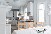 Christmas decorations on dining table and white kitchen in open-plan interior