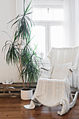 White knitted blanket on rocking chair next to potted palm