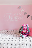 Soft toy on bed against pink wall in girl's bedroom