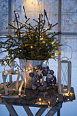 Christmas arrangement with fair lights on small wooden table in front of window