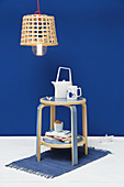 Side table with shelf made from stool in front of royal-blue wall
