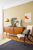 Armchair and retro sideboard in living room