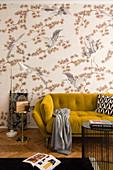 Senfgelbes Sofa vor tapezierter Wand im Wohnzimmer