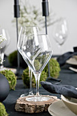 Wine glasses on wooden coasters on set table
