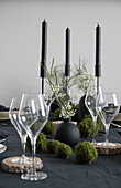 Weingläser auf Baumscheibe als Untersetzer und DIY-Mooskugeln auf gedecktem Tisch