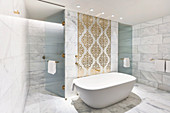 Marble tiles and ornate pattern on wall above bathtub in luxurious bathroom