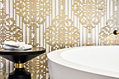 Ornate pattern of gold and white mosaic tiles behind bathtub