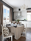 Dining table with linen tablecloth and chairs in bright kitchen