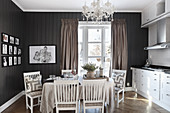 Dining table with linen tablecloth and chairs below chandelier in kitchen with dark walls