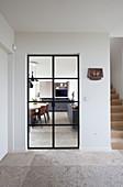 Blick vom Flur mit Steinboden durch eine Glastür in die Wohnküche