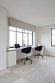 Zwei Bürostühle am eingebauten Schreibtisch unter dem Fenster
