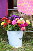 Brightly coloured bouquet of autumn flowers in metal bucket