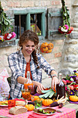 Young woman at table set for harvest festival in bright colours