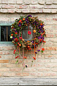 Autumnal wreath of flowers with test tubes hung from ribbons on brick wall