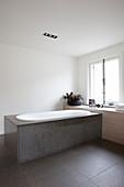Bathtub clad with stone panels below window