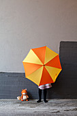 Girl hiding behind yellow and orange umbrella