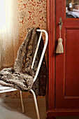Crocheted blanket on metal chair next to wooden door with tassel on key