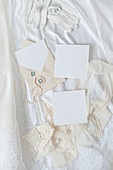 White note paper, decorated envelopes, pearl necklace and gloves lying on wedding dress