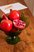 Whole and halved pomegranates in glass bowl