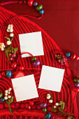 Wooden beads and white squares of paper on red surfae