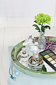 Perfume bottles, bracelets, green chrysanthemum in glass vase and eyeshadow palette on tray
