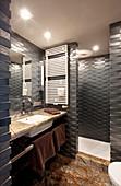 Strukturierte Wand mit dunklen Fliesen im kleinen Badezimmer