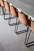 Brown chairs with metal frames at long dining table on stone floor