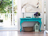 Turquoise blue lacquered table with hydrangeas, books and table lamp