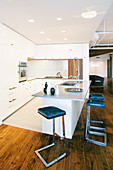 Cantilever barstools in modern, open-plan kitchen in loft apartment
