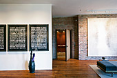 Three typographical artworks in modern loft apartment with brick walls