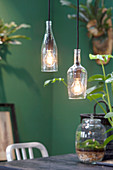 Two glass lampshades made from cut-off wine bottles