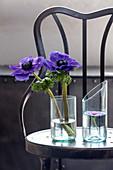 Blaue Anemonen in abgeschnittenen Flaschen als Vasen