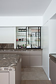 Kitchen shelves with open sliding glass door and base cabinet with marble worksurfaces