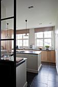 Blick auf Mittelblock und Unterschrank mit Holzfront vor Fenster in eleganter Küche