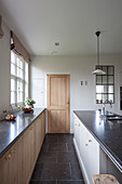 Base units with wooden doors below window and island counter in kitchen with white walls and black floor tiles