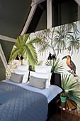 Doppelbett mit blauer Tagesdecke an Wand mit Dschungelmotiv